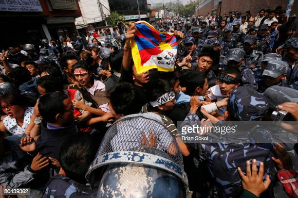 Tibetan protester holds aloft a Tibetan flag before being forcibly detained by Nepali police during a proTibetan protest outside of the Chinese...