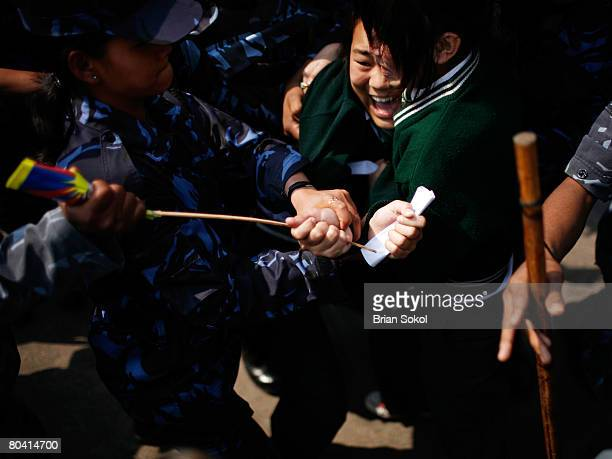 Tibetan school girls cling to one another as Nepali police attempt to detain them and wrestle a Tibetan flag from one's hand during a proTibet peace...