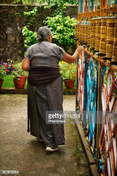 tibetan senior woman touching prayer wheels begging for good health - pokhara stock pictures, royalty-free photos & images