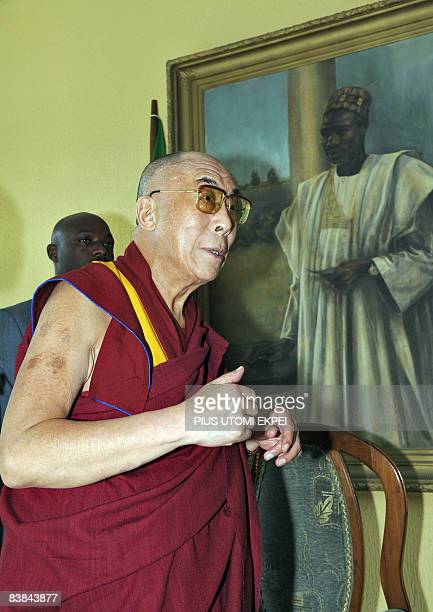 Tibetan spiritual leader Dalai Lama gets explanations about the painting representing a portraiture of Nigeria's first Prime Minister Abubakar Tafawa...