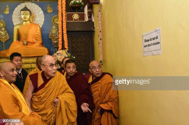 Tibetan spiritual leader the Dalai Lama and his entourage look at a sign warning against sitting too long at Mahabodhi Temple during his visit to...