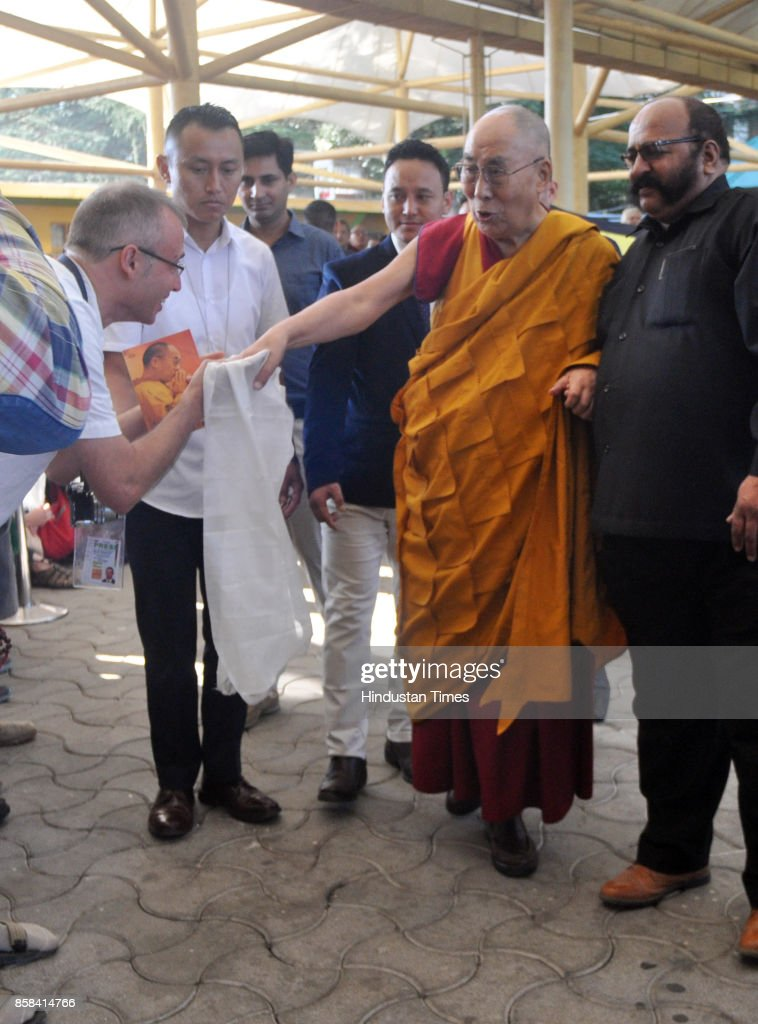 Tibetan spiritual leader the Dalai Lama, left in yellow robe, greets devotees as he arrives to give a religious talk at the Tsuglakhang Temple on October 6, 2017 in Dharamsala, India.
