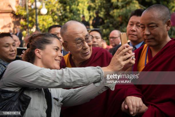 Tibetan spiritual leader the Dalai Lama poses for a selfie with a journalist as he arrives on September 20 2018 in Heidelberg western Germany The...