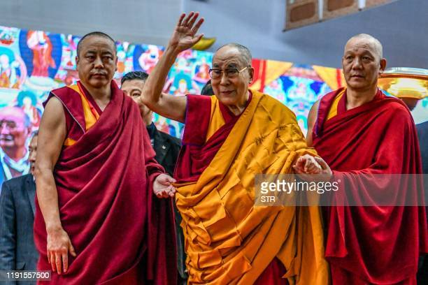 Tibetan spiritual leader the Dalai Lama waves to the crowd during the third day of a series of teachings in Bodhgaya on January 4 2020