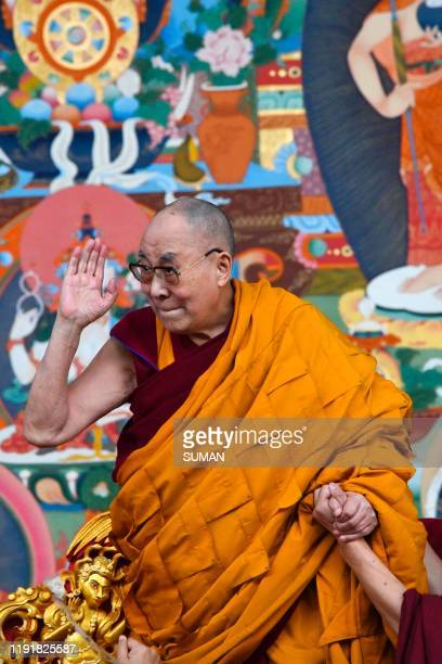 Tibetan spiritual leader the Dalai Lama waves to the crowd during the fourth day of a series of teachings in Bodhgaya on January 5, 2020.