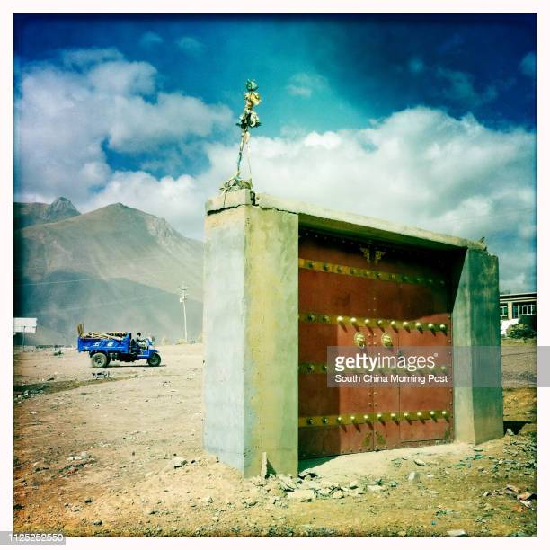 Tibetan style gate of a courtyard stands lonely on a piece of empty ground, after the earthquake devastated the whole house in Jiegu, Yushu, Qinghai,...