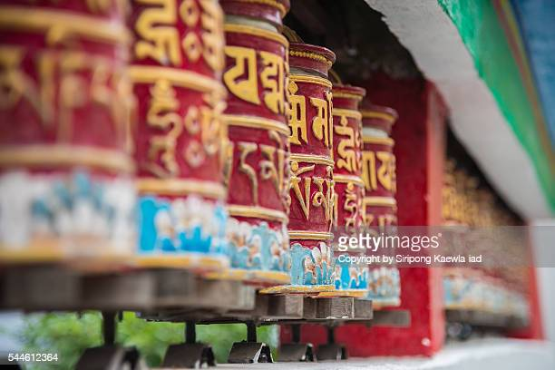 Tibetan style prayer wheel in a row