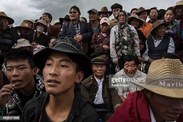 Tibetan watch as nomads perform skills during a riding competition at a local government sponsored festival on July 26 2015 on the Tibetan Plateau in...