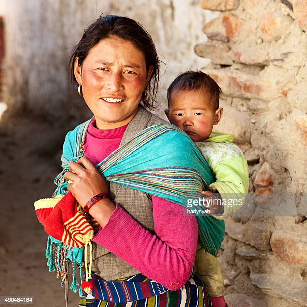 tibetan woman carrying her baby, upper mustang - lo manthang stock pictures, royalty-free photos & images