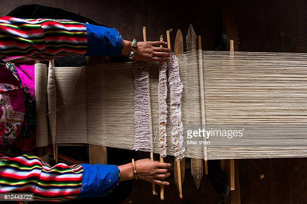 Tibetan woman dressed in traditional costume making hand-woven cloth at home