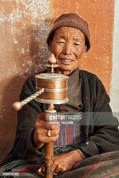 tibetan woman holding praying wheel, upper mustang - lo manthang stock pictures, royalty-free photos & images