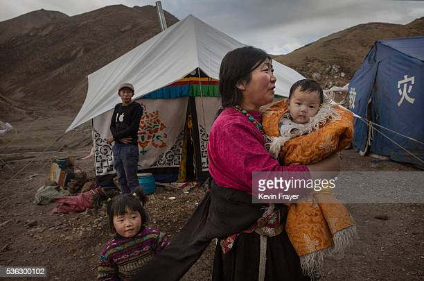 Tibetan woman holds a baby as she stands outside a tent at a temporary camp for cordycep pickers on May 23 2016 on the Tibetan Plateau near Zadoi in...