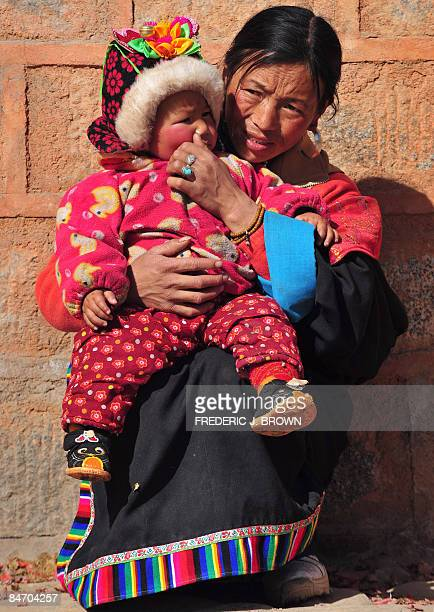 A Tibetan woman holds onto her child at the Nyentog Monastery also known as Nianduhu during celebrations for the ongoing Monlam or Great Prayer...