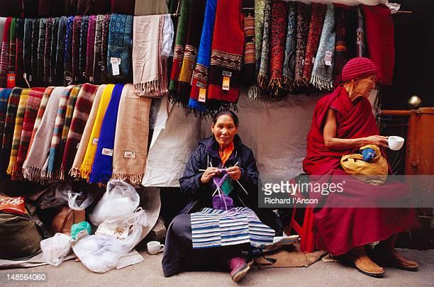 Tibetan woman knitting and nun at shawl stall on Jogibara Road.