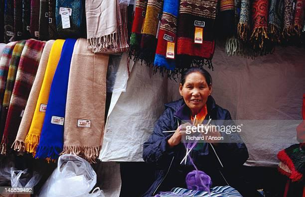 Tibetan woman knitting at shawl stall on Jogibara Road.