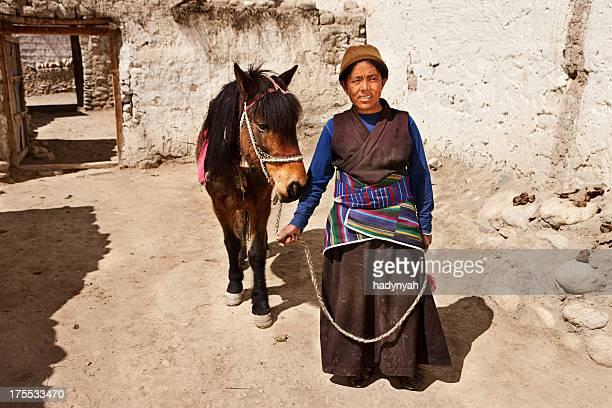 Tibetan woman leads her horse