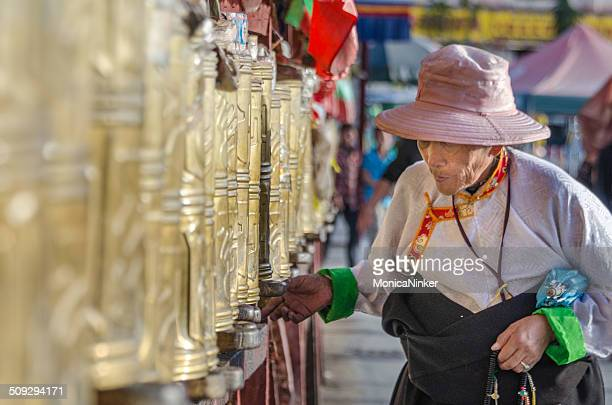 Tibetan woman spinning Prayer Wheels