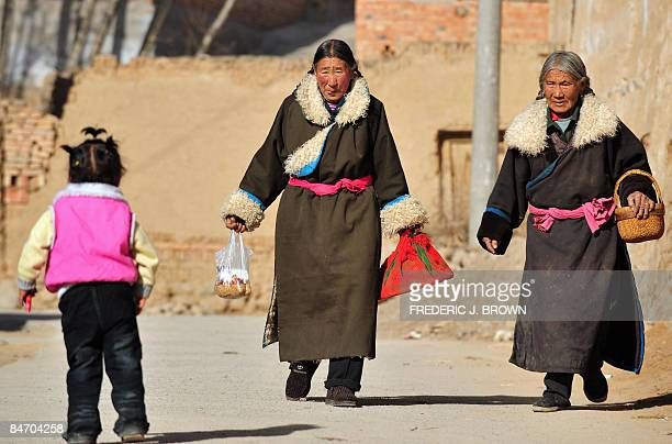 A Tibetan woman sticks out her tongue in a customary greeting while approaching a child at the Nyentog Monastery also known as Nianduhu during...