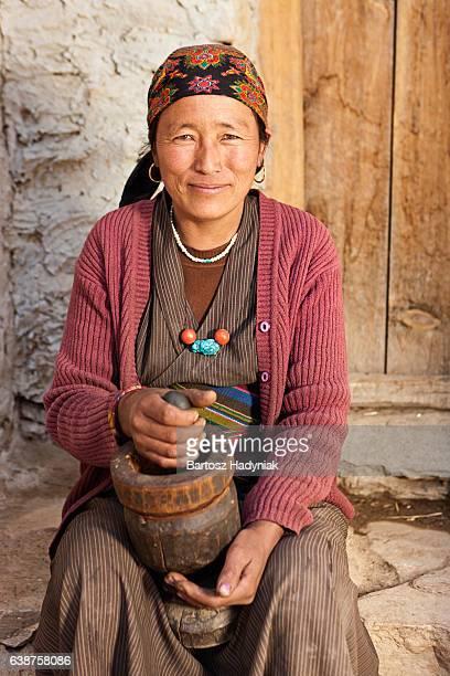 Tibetan woman using a mortar to make  flour. Mustang, Nepal