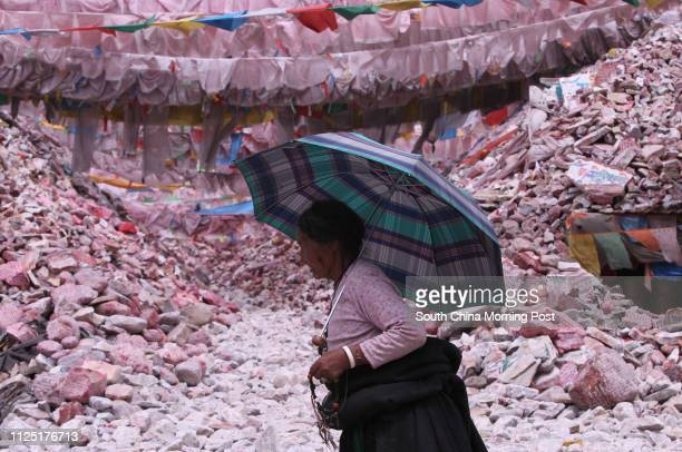 Tibetan woman walks in front of the Gyanag Mani Wall, the largest mani stone wall in the world, in Jiegu, Yushu, Qinghai, April 11, 2011. A...