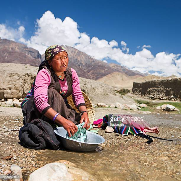Tibetan woman washing clothes in the river. Mustang.