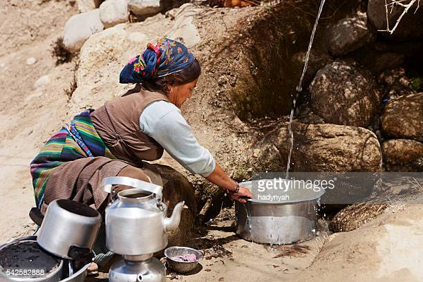 tibetan woman washing dishes. mustang, nepal - lo manthang stock pictures, royalty-free photos & images