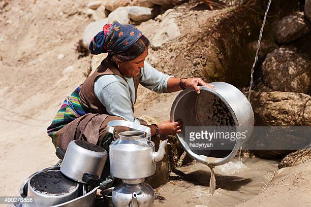 tibetan woman washing dishes. mustang - lo manthang stock pictures, royalty-free photos & images