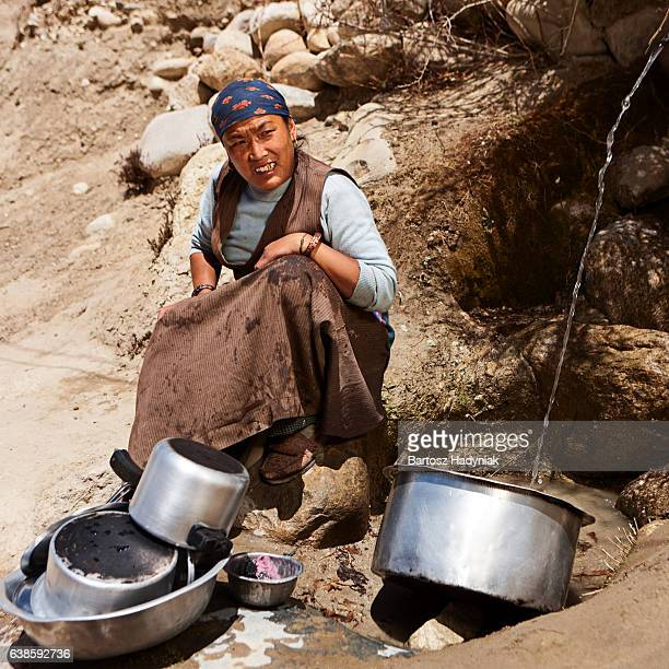 Tibetan woman washing dishes. Mustang
