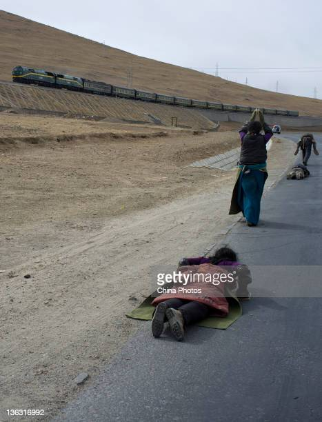 Tibetan women pray to make pilgrimage to Lhasa on a road along the QinghaiTibet railway on January 1 2012 in Damxung County of Tibet Autonomous...