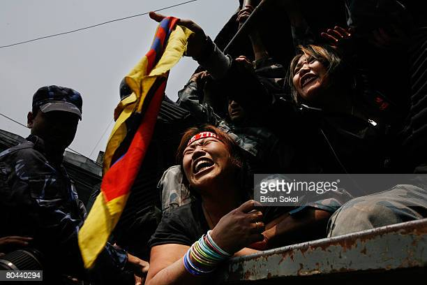 Tibetan women shout Free Tibet as one waves a Tibetan flag from the back of a Nepali police vehicle after being forcibly detained by Nepali police...