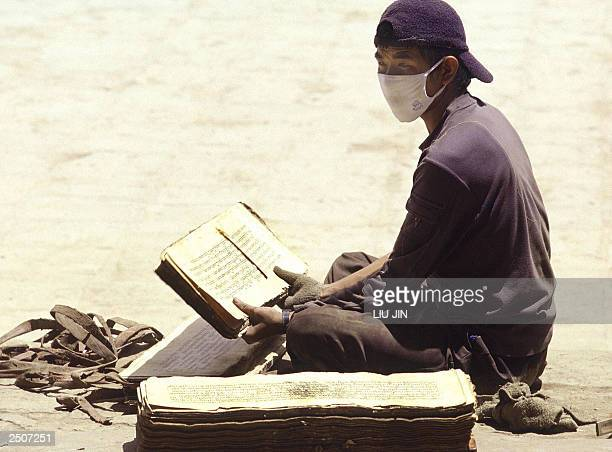 A Tibetan worker tidies the fivehundred history scriptures at an entrance of thr main chapel of the Pelkor Chode monastery in the county of Gyantse...