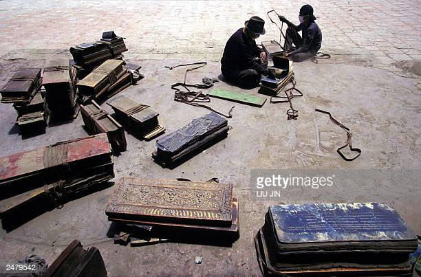 Tibetan workers sort the fivehundred year old history scriptures at the Pelkor Chode monastery in the county of Gyantse in Tibetan Autonomous Region...