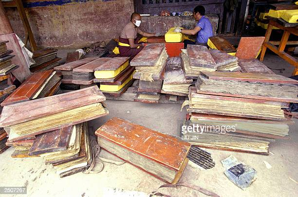 Tibetan workers wrap a book of history scriptures behind such books at the Pelkor Chode monastery in the county of Gyantse in Tibetan Autonomous...