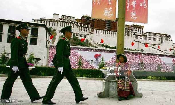 Tibetan worshiper looks at Chinese police officer patrolling in front of Potala Palace ahead of the Beijing Olympic Torch relay on June 20, 2008 in...