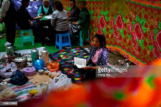 Tibetan young girl wears a clothes of the American flag pattern reading a Chinese character book while her families gather to play mahjong during the...