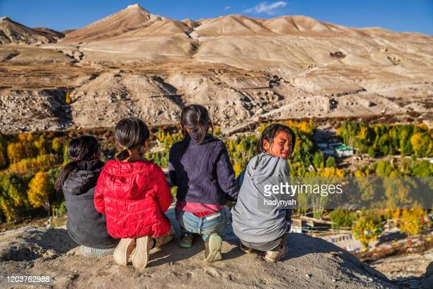 tibetan young girls looking at the view near lo manthang, upper mustang, nepal - tibet stock pictures, royalty-free photos & images