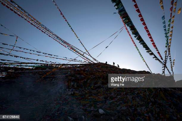 Tibetans put prayer flags on the top of a mountain on April 27 2017 in LhasaTibet Autonomous Region China