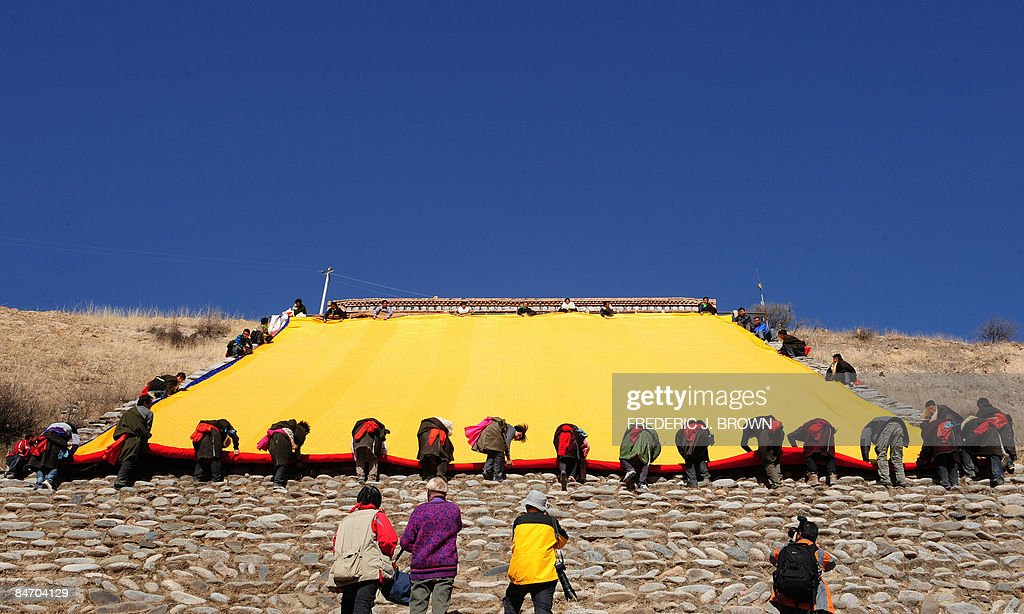 Tibetans roll up a thanka following the : News Photo
