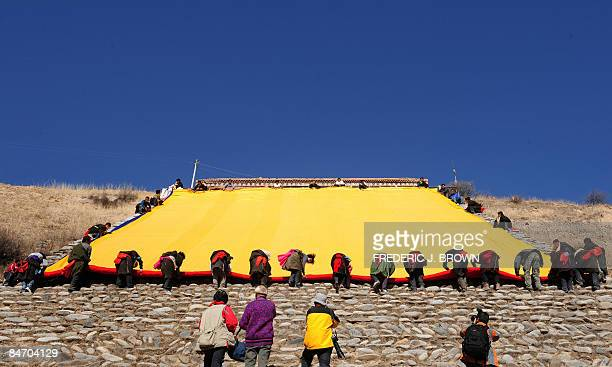 Tibetans roll up a thanka following the Sunning of the Buddha when a huge silk thanka showing the image of Sakyamuni the founder of Buddhism is...