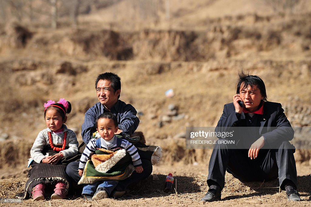 Tibetans sit in the fields for a view of : News Photo
