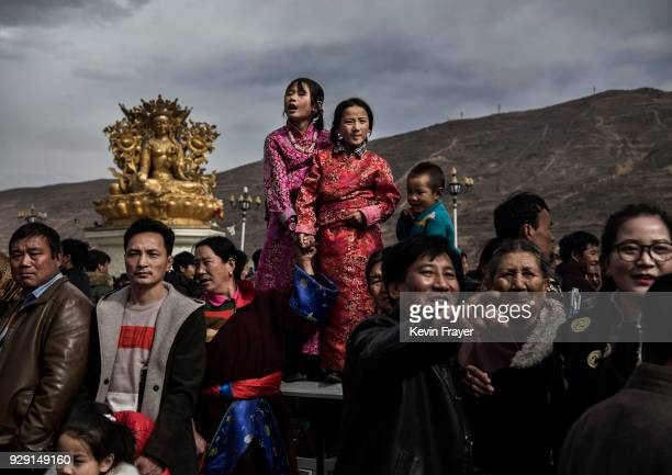 Tibetans watch as Buddhist Monks of the Gelug or Yellow Hat school carry a rolled up giant thangka not seen before unfurling it on a mountain side at...