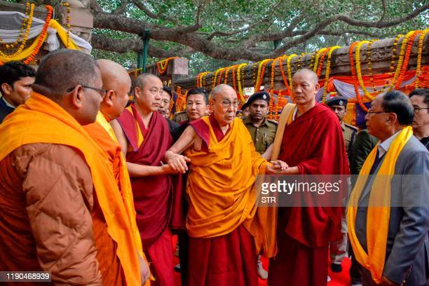 Tibetian spiritual leader the Dalai Lama is helped as he walks on a visit to the sacred Bodhi tree at the world heritage Mahabodhi temple in Bodhgaya...
