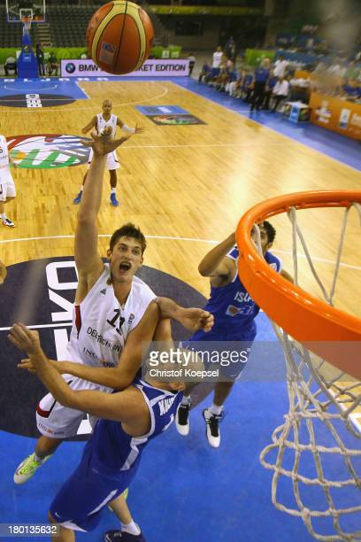 Tibor Pleiss of Gemany shoots over Ido Kozikaro of Israel during the FIBA European Championships 2013 first round group A match between Germany and...