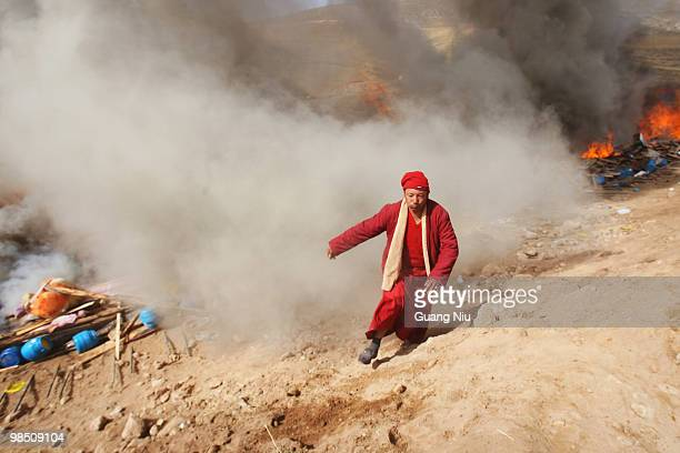 Tibrtan monk runs away after carrying a dead body to a fire funeral following a strong earthquake on Jiegu toweship of China's Qinghai province just...