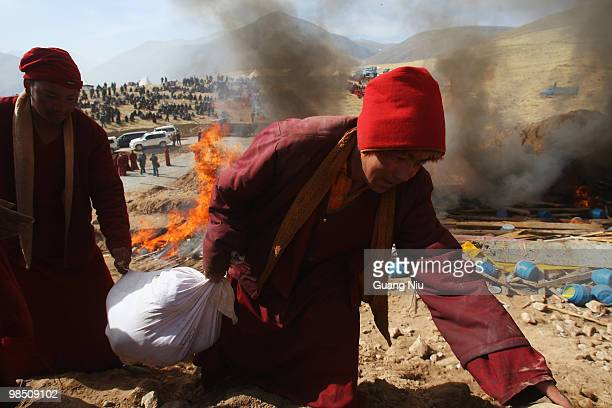 Tibrtan monks carry a dead body to a fire funeral following a strong earthquake on Jiegu toweship of China's Qinghai province just on April 17, 2010...