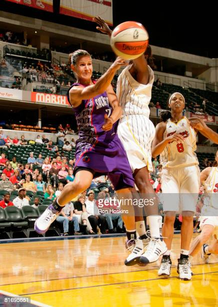 Ticha Penicheiro of the Sacramento Monarchs passes the ball around an Indiana Fever defender at Conseco Fieldhouse June 24 2008 in Indianapolis...