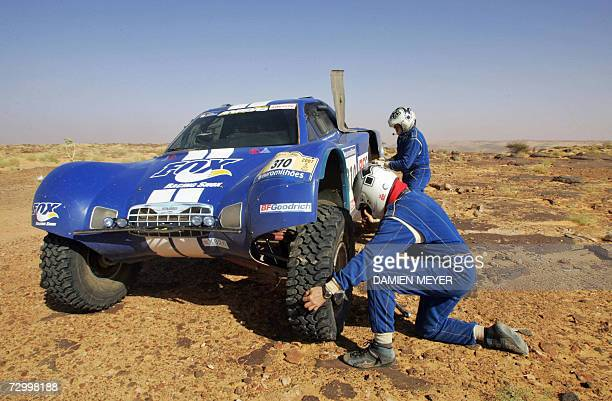 France's driver JeanLouis Schlesser and teammate Arnaud Debron change a wheel of their FordSchlesser after a puncture during the eighth stage of the...