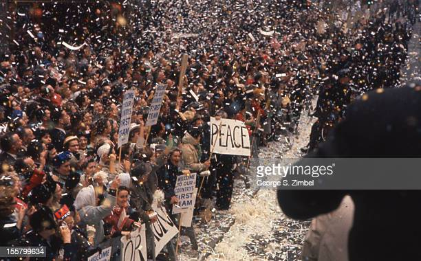 Ticker tape and confetti showers onto a crowd behind police barricades who cheer at an outdoor Repulican Presidental campaign rally New York New York...