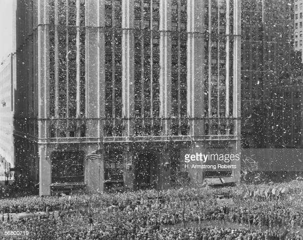 Ticker tape parade passing Woolworth Building in New York City