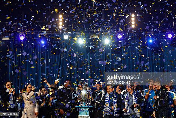 Tickertape falls onto the Leicester City football team as they stand with the Premier league trophy during a victory celebration in front of fans in...